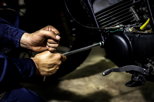 People use hand are repairing a motorcycle use a wrench to work.