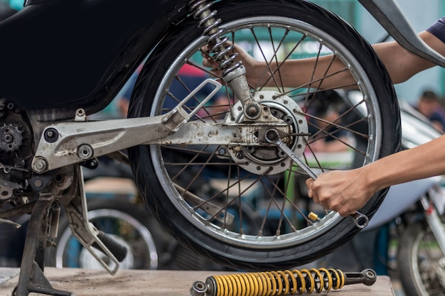 People use hand are repairing a motorcycle use a wrench to work