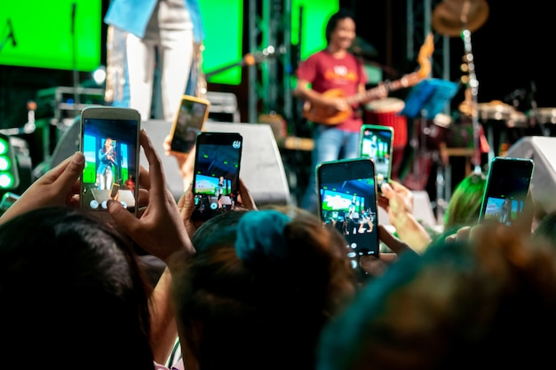 People use mobile phones to live or take pictures at concerts, with bright lights at night.