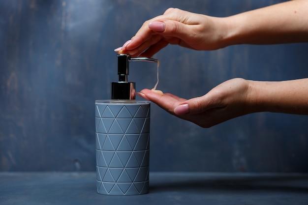人々は灰色のテーブルに灰色の金属キャップが付いた石鹸ディスペンサーを使用します
