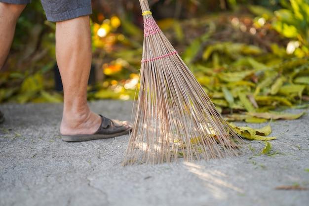 Люди используют метлу подметайте листья во дворе, чтобы убрать.