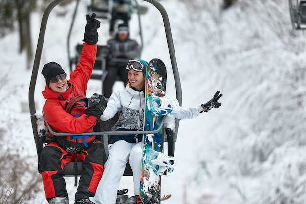 Люди, использующие кресельный подъемник на горнолыжном курорте