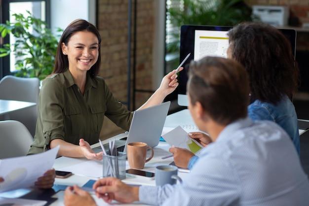 Люди, использующие цифровое устройство во время встречи