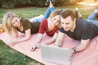 People using laptop on picnic
