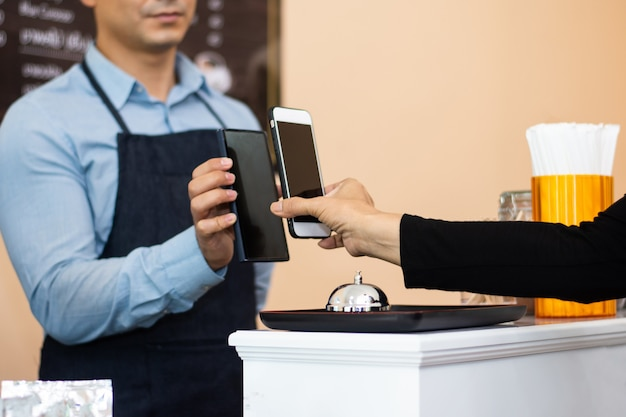 People using smartphone mobile banking scan qr code to pay in shop