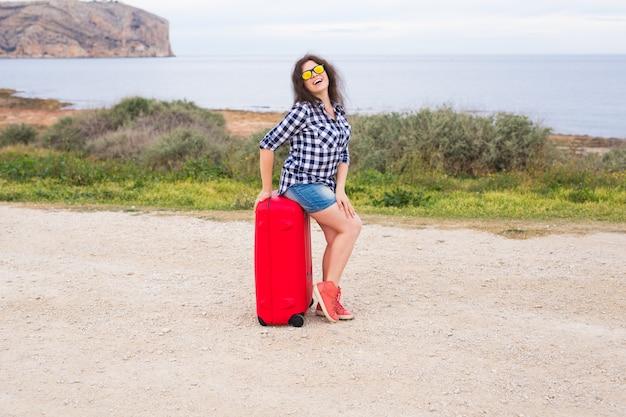 人、休暇、旅行のコンセプト。海を背景にスーツケースに座っている美しい若い女性。