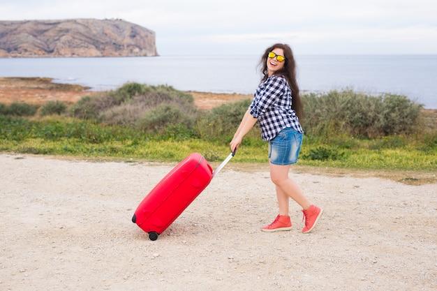 人、休暇、旅行のコンセプト-海面にスーツケースを持って立っている美しい若い女性。
