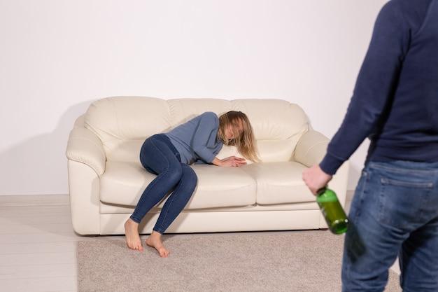 Концепция людей, насилия и жестокого обращения - мужчина пьет алкоголь, пока жена лежит на диване