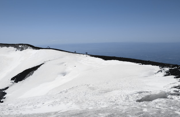 People on volcano mount etna crater