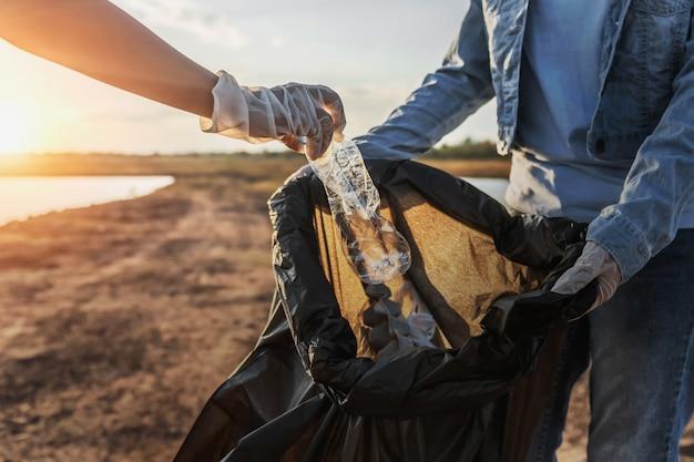 People volunteer keeping garbage plastic bottle into black bag at park near river in sunset
