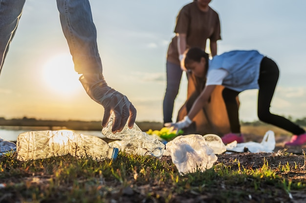 People volunteer keeping garbage plastic bottle into black bag at park near river in sunset