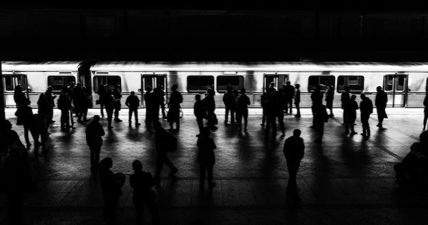 Люди ждут поезд на платформе