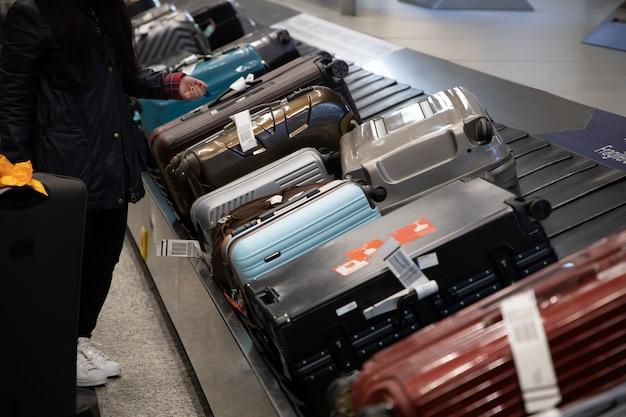 공항에서 컨베이어 벨트에 짐을 기다리는 사람들
