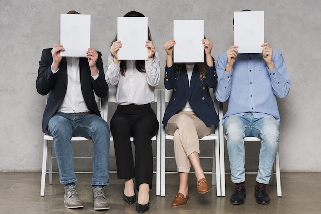 People waiting for their job interviews holding blank papers Premium Photo