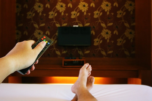 People wake up in bed and turn on the tv with a remote control in the room