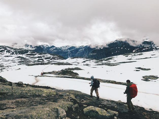 People walk across the mountains covered with snow