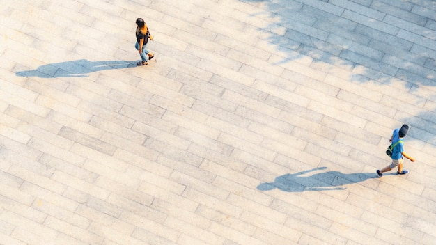 People walk on across the pedestrian concrete landscape with black silhouette shadow on ground