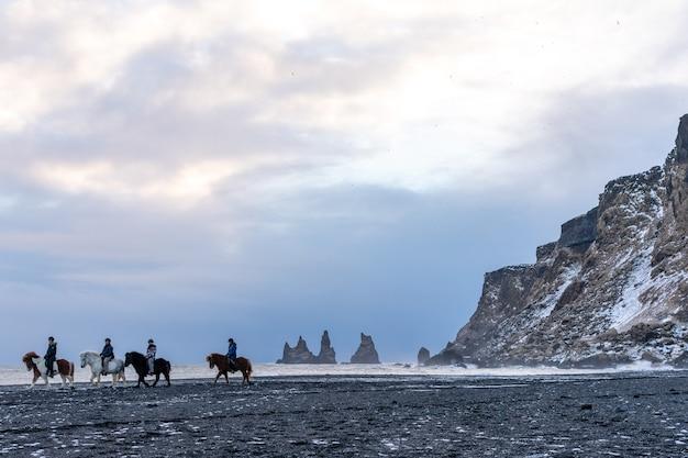 Люди уезжают на лошадях по черному пляжу атлантического океана на рейнисфьяре.