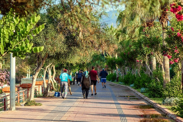 Люди гуляют ранним утром по набережной.