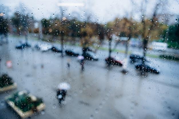 Люди ходят под дождем по улице, вид через мокрое окно