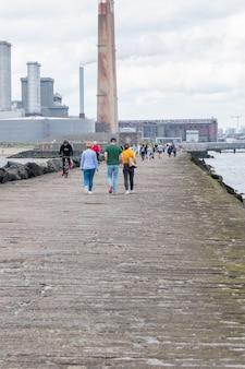 Люди идут по большой южной прогулке к маяку поллбег.