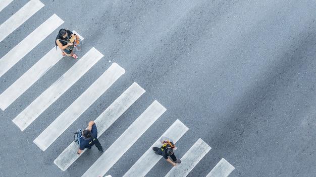 人々は街の通りの歩行者用交差点を歩いている。