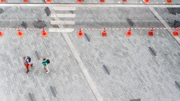 人々は舗装コンクリートの上を歩行者の街の通りの歩道を歩きます。
