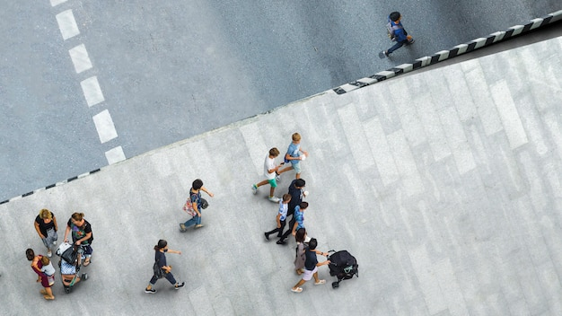 People walk on the pedestrian street walkway with the teenage young man and the group of family with little child.