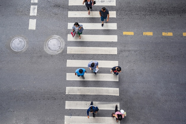 People walk on street in the city over pedestrian crossing traffic road