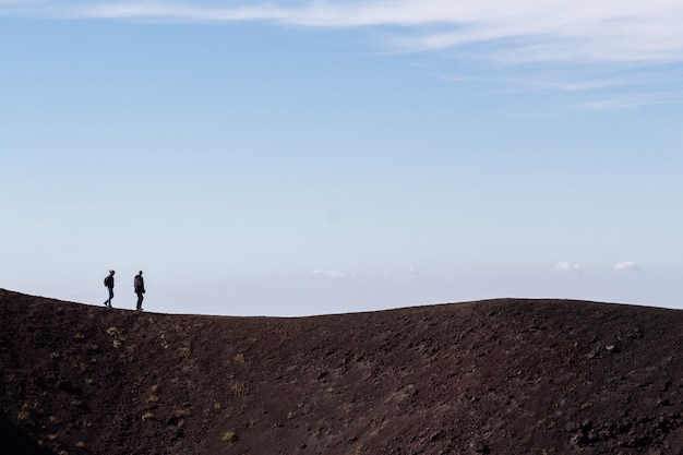 People walking along etna volcano