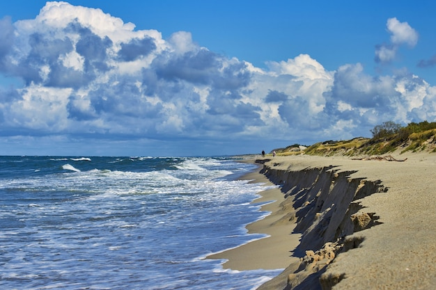 Люди, идущие вдоль прибоя на фоне красивых облаков и дюн