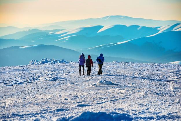 雪に覆われた冬の山々の日没で歩く人々