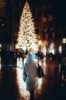 Persone che camminano in città con decorazioni natalizie