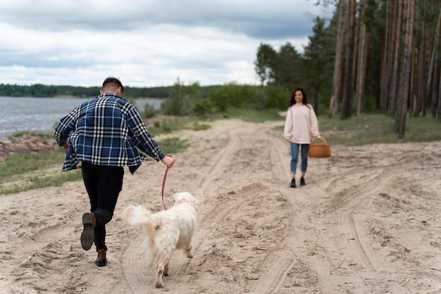 해변 전체 샷에 개를 걷는 사람들