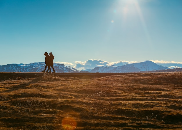 People walking in a field with beautiful snowy hills