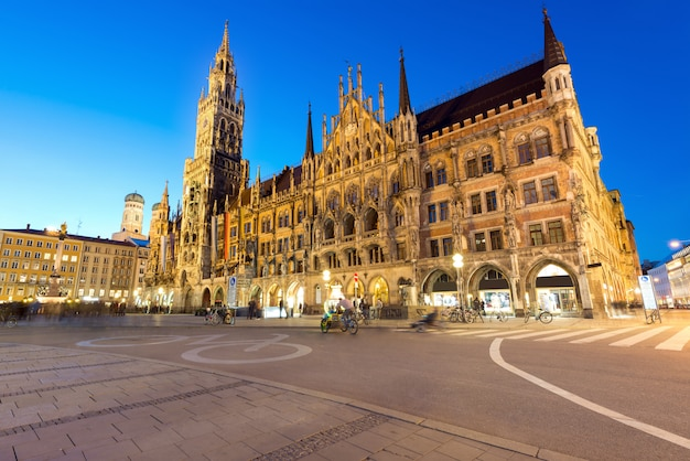 People walking at marienplatz square and munich city hall in night in munich, germany.