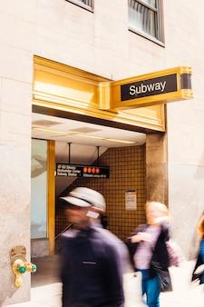 地下鉄の看板の近くを歩く人