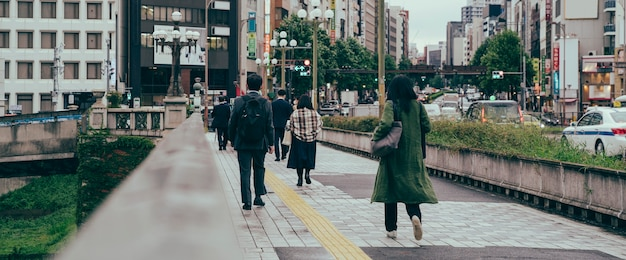 Люди, идущие по мосту через воду в городе