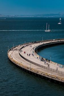 낮 동안 푸른 바다 위에 콘크리트 다리를 걷는 사람들