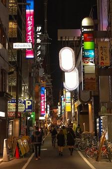 ライトのある日本の通りを歩く人