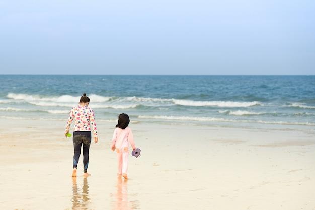 海の近くのビーチを歩いている人
