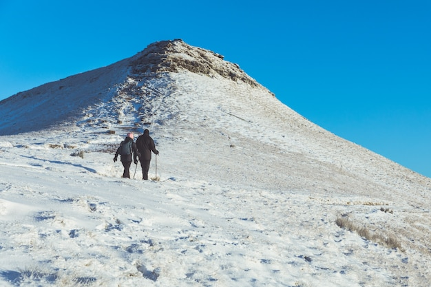 People walking on the snow in a mountain path