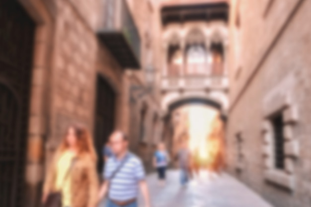 People walking on a street along ancient vintage architecture in an old town.