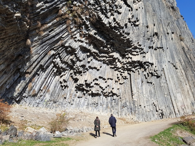 Люди, идущие по тропинке в гарнинском ущелье под солнечным светом в армении