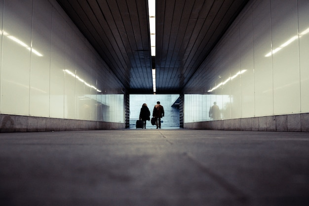 People walking through an underground subway corridor with suitcases trolley.