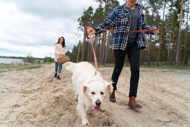해변에 강아지와 함께 산책하는 사람들을 닫습니다.