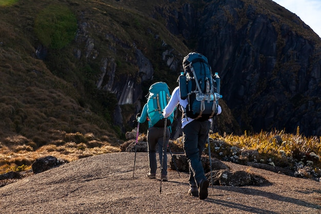 People walking with great backpacks in mountain landscape - trekking hiking mountaneering in mantiqueira range brazil