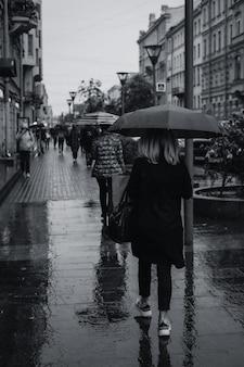 秋の雨の中、傘をさして歩く人
