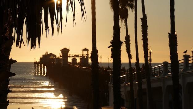 미국 캘리포니아 나무 부두를 걷는 사람들. 오션 사이드 워터 프론트 휴가 관광 리조트. 오션 비치 여름 일몰 분위기입니다. 판자를 산책하는 흐릿한 군중. 원활한 루프 시네마그래프.