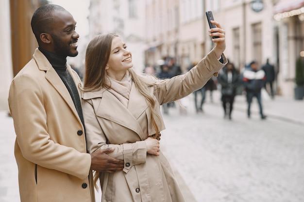 人々は外を歩きます。都市の混血。女性は電話を使います。